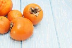 橙色颜色飞溅:未加工的果子:葡萄柚、桔子、普通话和柿子在浅兰的背景 库存图片