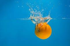 橙色飞溅在水中与蓝色背景 免版税库存图片