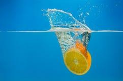 橙色飞溅在水中与蓝色背景 免版税库存照片