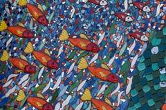 橙色鱼在大胆的蓝色和绿色马赛克墙壁引人注意 免版税库存照片
