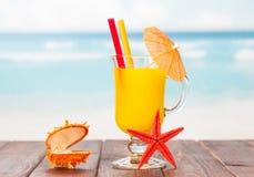 橙色鸡尾酒、海星和小箱有珍珠的在蓝色海 库存图片