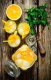 橙色鸡尾酒用伏特加酒、冰和薄荷叶在一张木桌上 免版税库存图片
