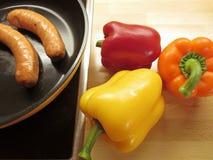 橙色,红色,染黄用绿色词根成熟响铃胡椒和烤香肠一种容易的膳食准备的,烹调 免版税库存照片