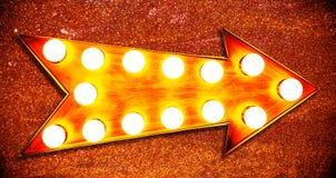 橙色,黄色和带红色与发光的电灯泡的颜色葡萄酒明亮和五颜六色的被阐明的金属显示金黄箭头标志 库存照片