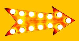 橙色,黄色和带红色与发光的轻的bul的颜色葡萄酒明亮和五颜六色的被阐明的金属显示橙色箭头标志 库存照片