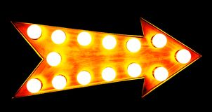 橙色,黄色和带红色金黄与发光的电灯泡的葡萄酒明亮和五颜六色的被阐明的金属显示箭头标志 免版税库存照片