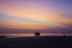 橙色黎明前天空和一条搁浅的孤立小船 库存照片