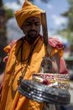 橙色绳索的耍蛇者在街道上执行 库存图片