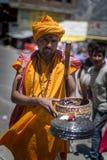 橙色绳索的耍蛇者在街道上执行 免版税库存图片