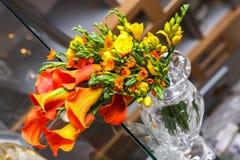橙色水芋百合和其他花五颜六色的花束在桌上 免版税库存照片