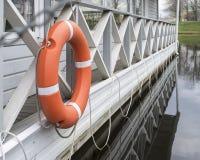 橙色lifebuoy在一个木码头 免版税库存图片