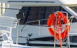 橙色lifebuoy在小船,人生一个根本的工具一边 库存图片
