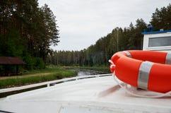 橙色lifebuoy在沿河的一个船航行在森林附近 库存图片