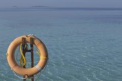 橙色lifebuoy在蓝色海的岸 免版税库存照片