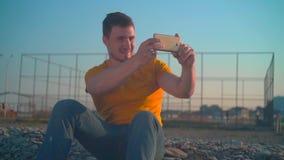 橙色T恤杉和牛仔裤的一年轻人由海在春天 人在电话做一张照片 股票录像