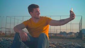 橙色T恤杉和牛仔裤的一年轻人由海在春天 人在电话做一张照片 影视素材