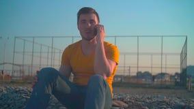橙色T恤杉和牛仔裤的一年轻人由海在春天 人在电话谈话 股票录像
