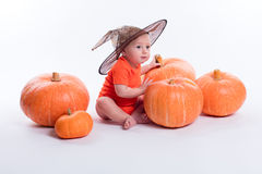 橙色T恤杉的婴孩在坐在witche的白色背景 免版税库存照片