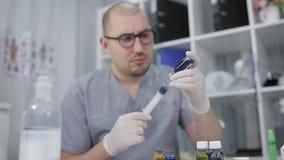 橡胶手套的一位医生拨液体试剂入注射器 实验员举办实验室研究 影视素材