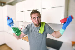 橡胶手套的年轻哀伤的人清洗与洗涤剂喷雾清洗和做家庭厨房水槽的 库存图片