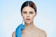 橡胶手套的年轻美丽的妇女在蓝色背景拿着一个注射器,医学,整形外科医生 免版税库存照片