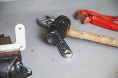 橡胶短槌和活络扳子板钳在工作凳说谎 免版税库存照片