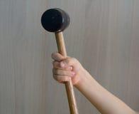 橡胶短槌在孩子的手上,木把柄的 免版税库存照片