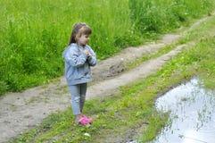 橡胶鞋子的小女孩在水坑附近做一个愿望在夏天森林里 库存图片