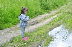 橡胶鞋子的小女孩在水坑附近做一个愿望在夏天森林里 免版税库存图片