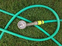 橡胶水管和喷雾器在草坪 免版税库存图片