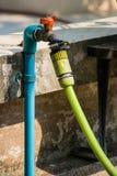 橡胶水管附加在篱芭里面的一个龙头 图库摄影
