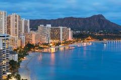 檀香山市和威基基海滩在晚上 免版税图库摄影