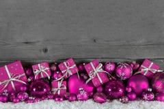欢乐圣诞节框架:与桃红色的木背景提出  免版税库存图片