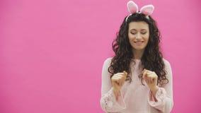 欢乐复活节节日 复活节兔子耳朵的微笑的年轻女人在跳跃和看拷贝的桃红色背景 影视素材