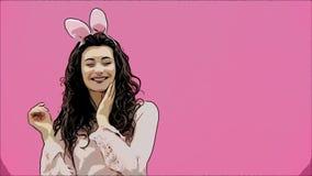 欢乐复活节节日 复活节兔子耳朵的微笑的年轻女人在跳跃和看拷贝的桃红色背景 股票录像