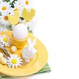 欢乐复活节桌设置用鸡蛋、白色兔子和花 图库摄影