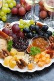欢乐开胃菜-乳酪、果子和果酱在板材,垂直 库存图片