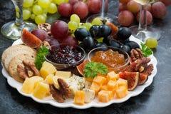 欢乐开胃菜-乳酪、果子和果酱在板材 库存照片