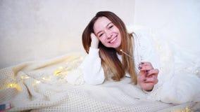 欢乐心情的迷人的女孩祝贺与新年` s假日,说谎在用毯子盖的地板上在明亮的屋子里 股票视频