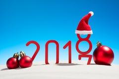 欢乐新年与圣诞节球的概念一个晴朗的热带海滩与在红色和拷贝空间的改变的日期2017年- 2018年  免版税库存照片