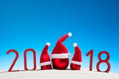 欢乐新年与圣诞节球的概念一个晴朗的热带海滩与2018年在红色和拷贝空间在蓝天 免版税库存照片