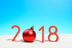 欢乐新年与圣诞节球的概念一个晴朗的热带海滩与2018年在红色和拷贝空间在蓝天 库存图片