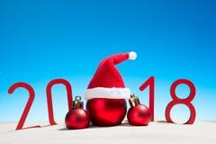 欢乐新年与圣诞节球的概念一个晴朗的热带海滩与2018年在红色和拷贝空间在蓝天 图库摄影