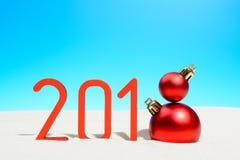 欢乐新年与圣诞节球的概念一个晴朗的热带海滩与2018年在红色和拷贝空间在蓝天 免版税库存图片