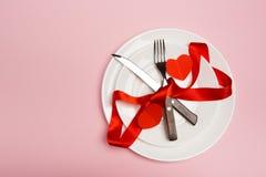 欢乐桌设置为与叉子,刀子,在红色背景的心脏的情人节 顶视图 - 图象 免版税库存照片