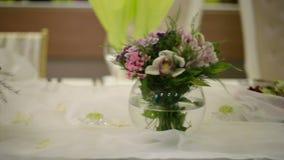 欢乐桌设置了与玻璃并且开花花束 股票录像