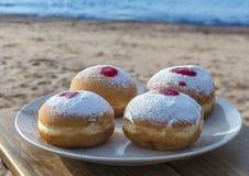 欢乐甜油炸圈饼用在红海的沙滩的果酱 免版税库存图片