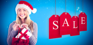 欢乐白肤金发的举行的圣诞节礼物和袋子的综合图象 免版税图库摄影