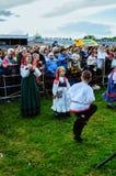 欢乐的人民有乐趣和跳舞,观看在阶段的表现在城市天在Veliky诺夫哥罗德,俄罗斯 免版税库存图片