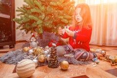 欢乐衣裳排序圣诞树玩具的美丽的白肤金发的女孩 免版税库存照片